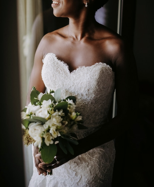 Windoの前に立っている魅力的なアフリカ系アメリカ人の花嫁の笑顔 無料写真
