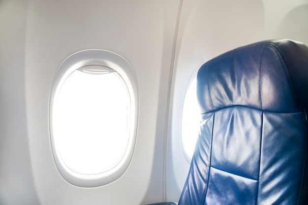Window in airplane with seats in the cabin Premium Photo