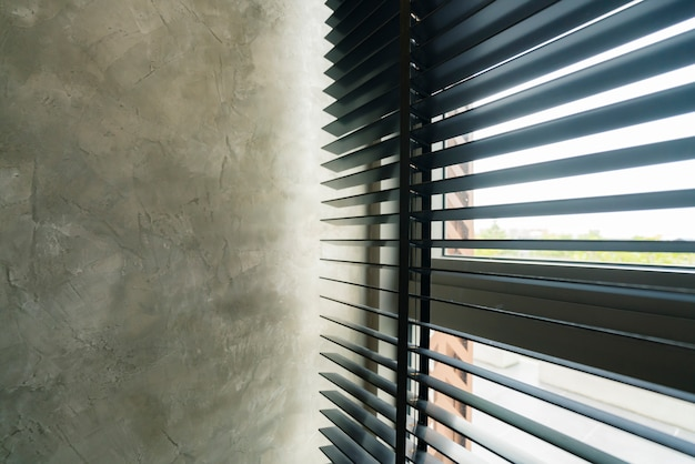 Window blind shutter with light shadow and concrete wall Premium Photo