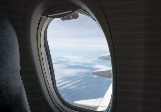 Window side of passenger with wing airplane flying Premium Photo
