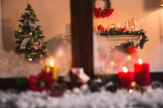 Window with candles and snow and a christmas scene background Free Photo