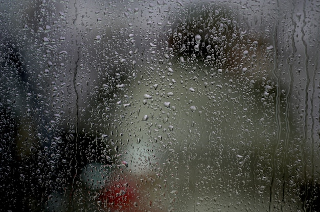 ライトの下で雨滴が付いている窓 無料写真