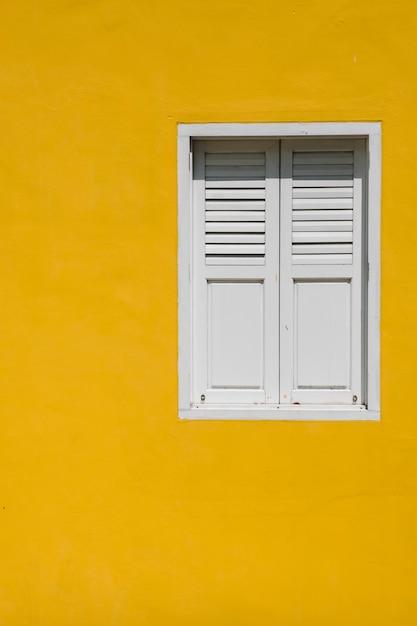 Window on yellow wall Free Photo