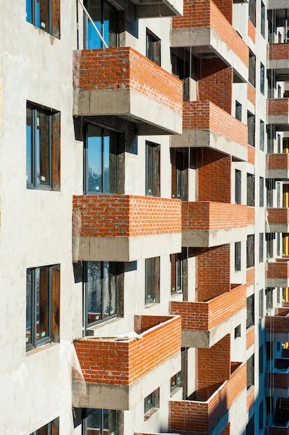 Окна и балконы из кирпича строящегося нового дома. монолитное строительство Premium Фотографии