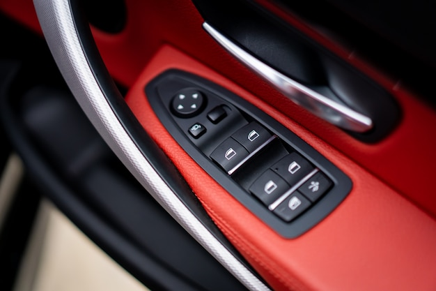 Windows and lock controller in the modern luxury car covered by beautiful red leather close up. Premium Photo