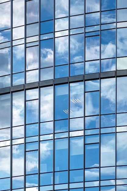 青い空と白い雲の反射と超高層ビルの窓 Premium写真