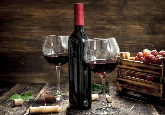 와인 배경. 포도 한 상자와 레드 와인입니다. 프리미엄 사진