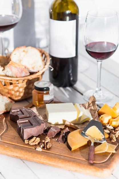 ワイン、バゲット、チーズの木製の背景 無料写真