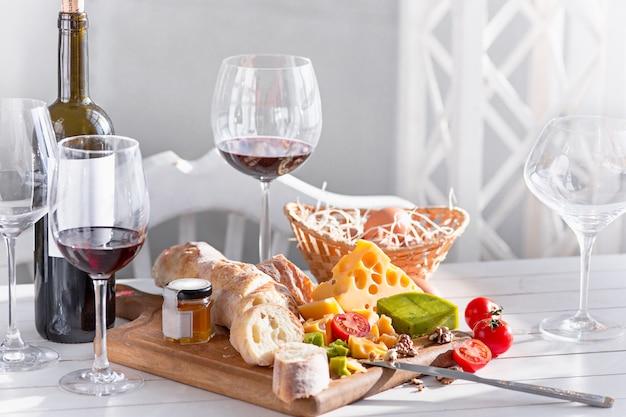 ワイン、バゲット、チーズ、木製テーブル 無料写真