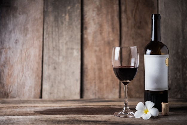 Wine bottle, glass and white flower on wood background Premium Photo