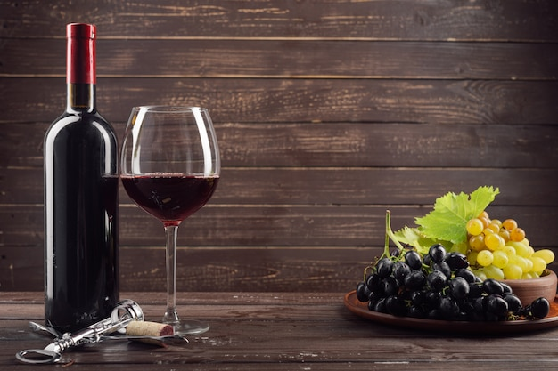 Wine bottle and grape on wooden table Premium Photo