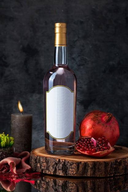 Винная бутылка со свечой, гранатом, растением и шарфом на деревянном куске Бесплатные Фотографии