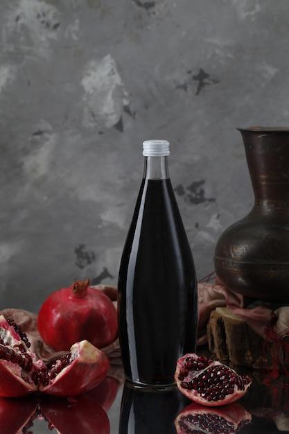 Бутылка вина с гранатами, вазой на шарфе и деревянным куском Бесплатные Фотографии