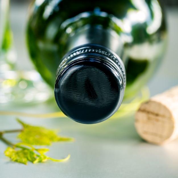 Wine bottle with vine and wine cork put on the board. Premium Photo