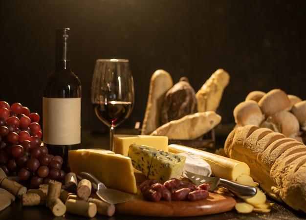 Wine, bread, grapes and cheese still life Premium Photo