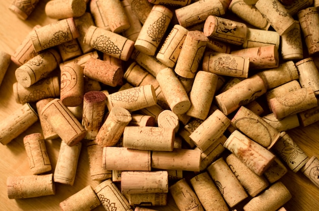wine-corks-heap-wooden-background_93314-1041.jpg