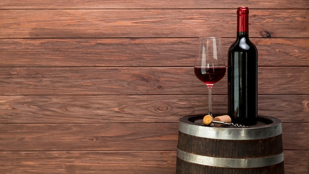 Wine glass and bottle on a barrel Free Photo