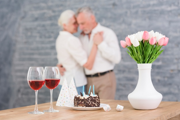 Wine glass; party hat; birthday cake and flower vase on table in front blurred couple dancing Free Photo