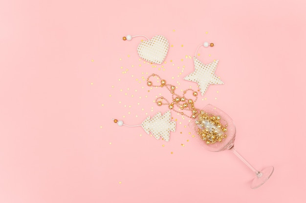 Wine glass poured out golden christmas decoration and confetti stars on pink new year, christmas, holiday concept Premium Photo