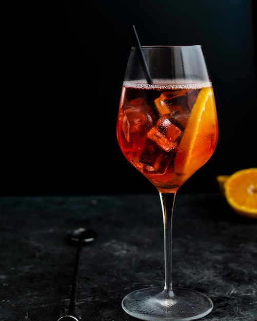Wine glass with aperol spritz, italian alcoholic cocktail on dark Premium Photo