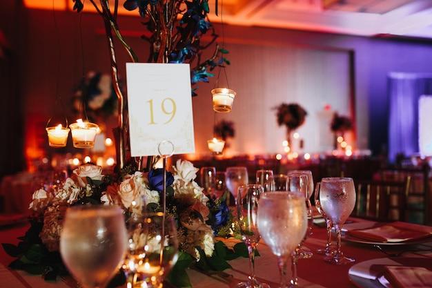 Bicchieri di vino sul tavolo servito con candele accendendo e numero del tavolo su di esso Foto Gratuite