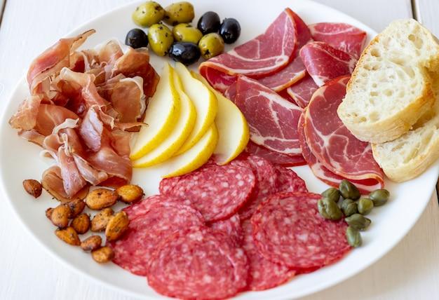 Винная закуска. прошутто, пармская ветчина, салями, миндаль, оливки, багет. antipasti. Premium Фотографии