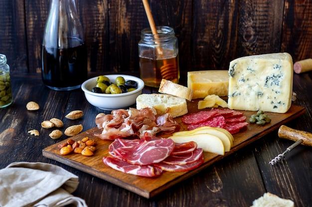 Винная закуска. прошутто, пармская ветчина, салями, миндаль, оливки, багет, голубой сыр, пармезан. antipasti. Premium Фотографии