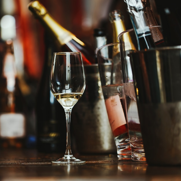 Wine tasting: a glass with the remains of wine is on the table next to the silver buckets. Premium Photo