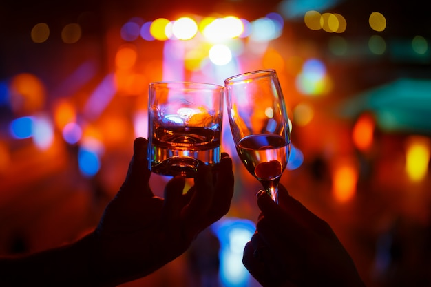 Wineglass of champagne in woman hand and a glass of whiskey in a man hand Premium Photo