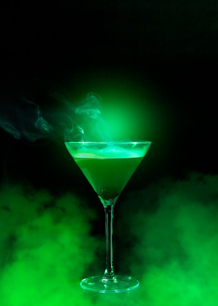 Wineglass with liquor and green smoke Free Photo