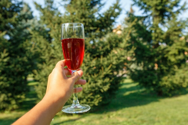 Wineglass with red champagne stand on wooden table at green summer park Premium Photo