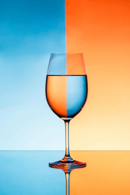 Bicchiere di vino con acqua sopra fondo blu ed arancio. Foto Gratuite