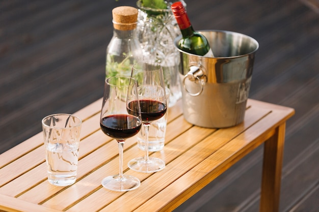 Wineglasses and ice bucket with wine bottle on small wooden table Free Photo
