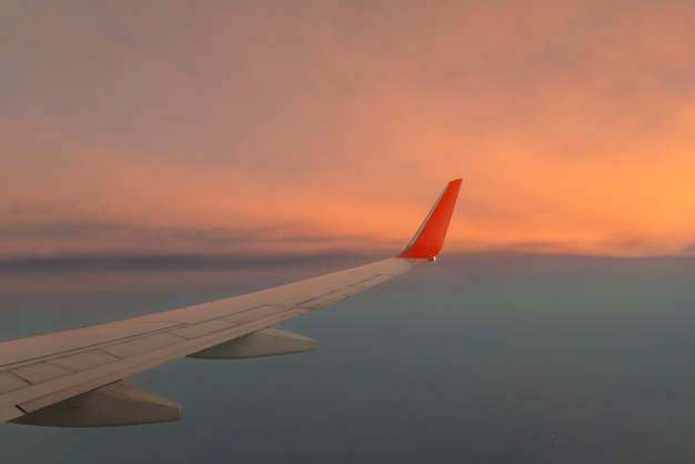 Wing airplane against the sunset sky above the cloud. Premium Photo