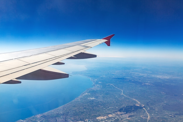 Wing of an airplane. aircraft wing on the clouds Premium Photo