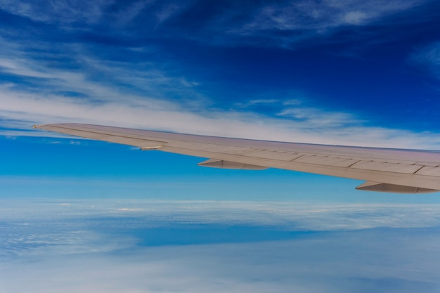 Wing of airplane flying above the clouds in the sky Premium Photo