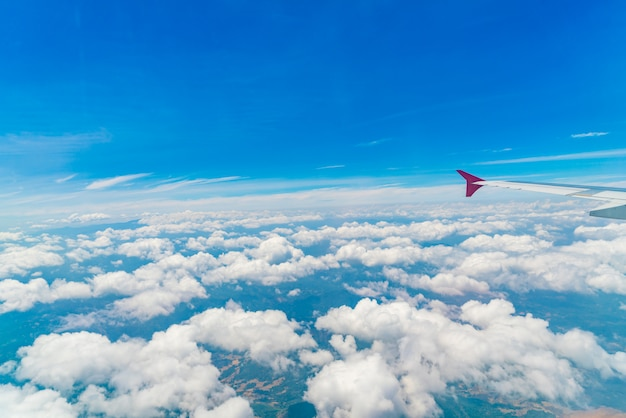 Wing of an airplane flying above the clouds . Premium Photo