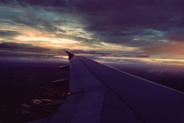 Wing of airplane flying above the dark rain clouds at sunset in bangkok Premium Photo