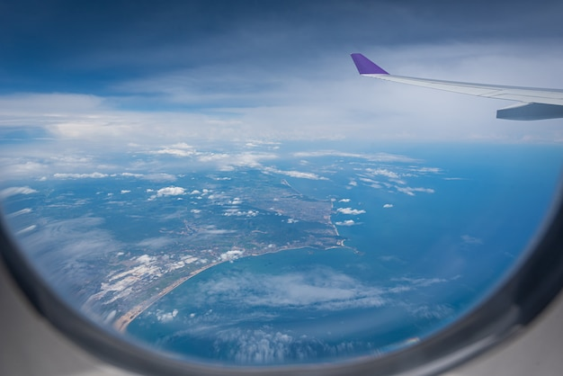 Wing of airplane flying above hong kong city background through the window. Premium Photo