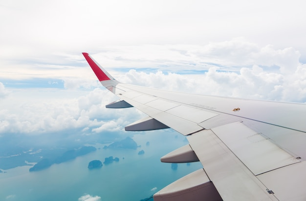 Wing of an airplane flying above sea and island Free Photo