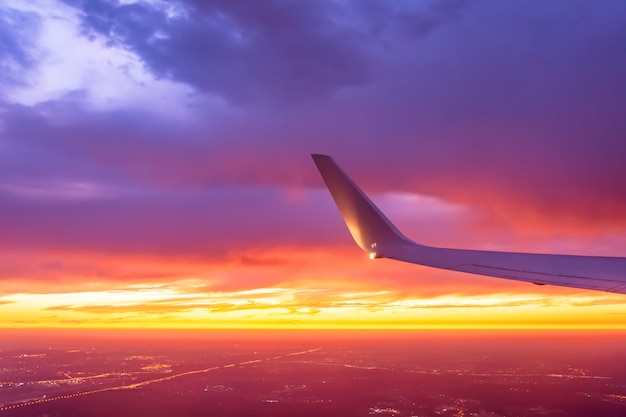 Wing of the plane lit by the sunset on a coloful sky. Premium Photo