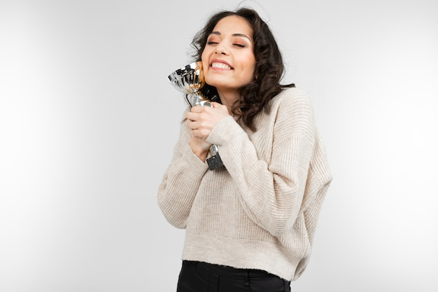 Winner girl holds her champion cup on gray background with copy space. Premium Photo