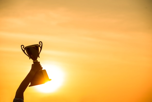 Winner win holding golden champion trophy cup prize Premium Photo