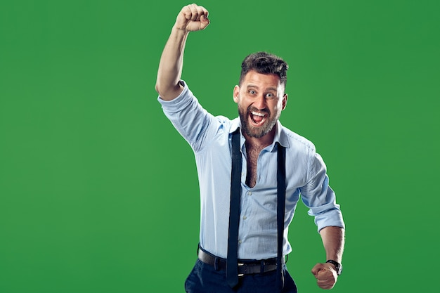 승리 성공 행복 한 사람이 승자가 되 고 축 하합니다. 녹색 벽에 백인 남성 모델의 동적 이미지. 승리, 기쁨 개념. 인간의 얼굴 감정 개념. 무료 사진