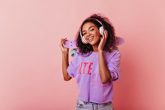 Winsome 평온한 흑인 소녀 듣는 음악. Jocund 아프리카 여성 모델 헤드폰에서 포즈의 스튜디오 샷. 무료 사진