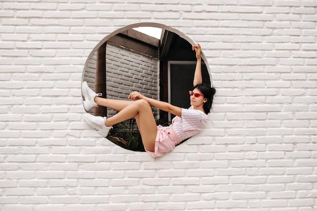 벽돌 된 벽에 앉아 Winsome 백인 여자입니다. 도시 배경에 포즈 기쁜 무두 질된 여자의 야외 샷. 무료 사진