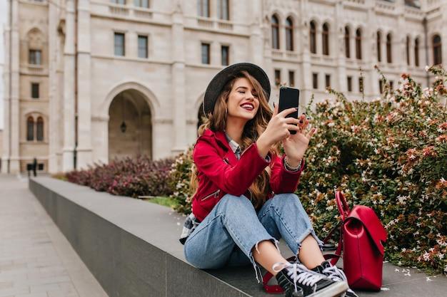 スマートフォンで通りに座って笑っているスポーツシューズの魅力的な女性 無料写真