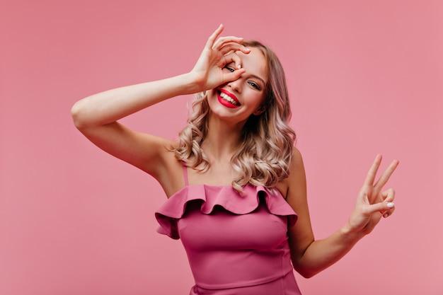 Очаровательная женщина со светлыми вьющимися волосами дурачится на розовой стене Бесплатные Фотографии