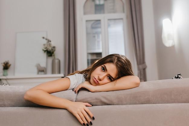 Обаятельная женщина с грустным выражением лица смотрит в камеру, лежа на удобном диване Бесплатные Фотографии
