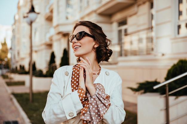 Giovane donna accattivante in eleganti occhiali da sole godendo una calda giornata autunnale. colpo esterno di allegra ragazza riccia in giacca bianca. Foto Gratuite